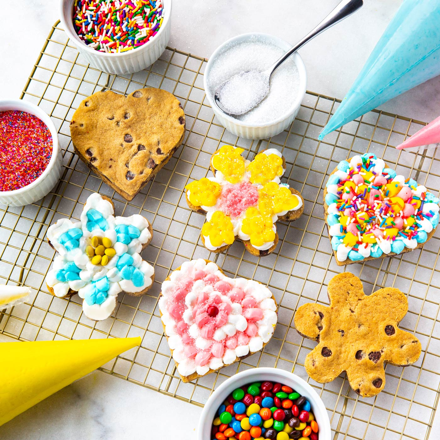 Three heart and three flower shaped cookies being decorated with icing, sprinkles, sugar, and m&ms