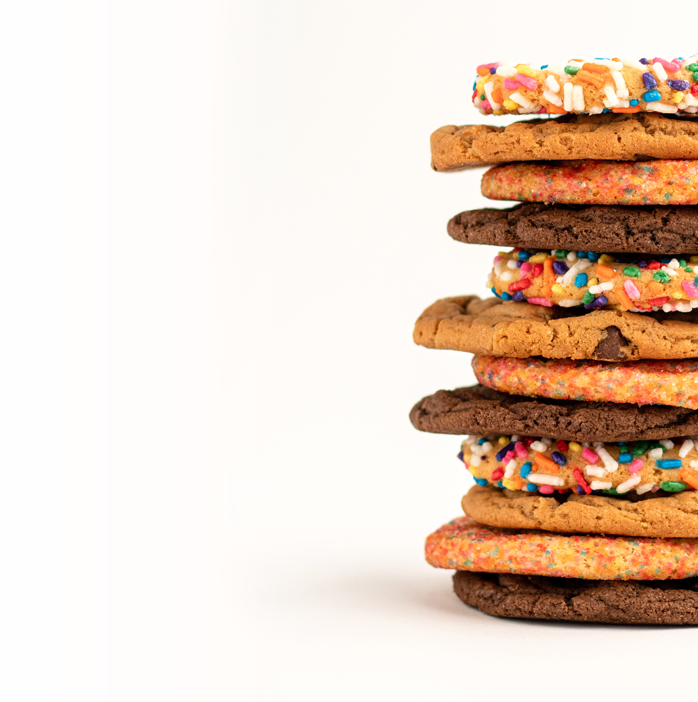 Picture of a stack of a dozen assorted cookies including birthday cake, original chocolate chip, sugar and double fudge cookies